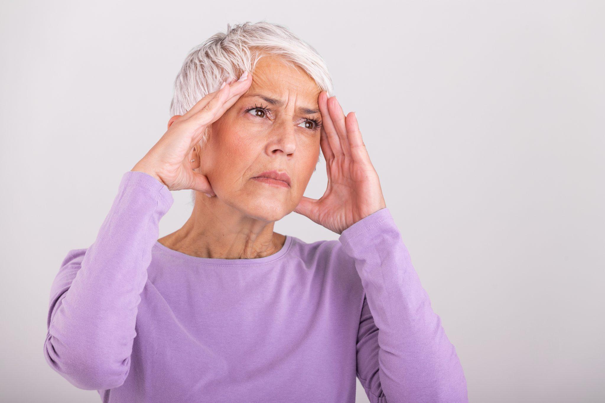 Senhora com dor de cabeça
